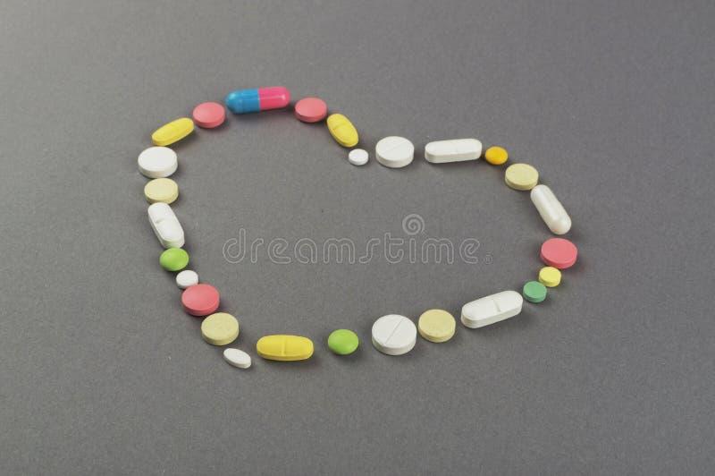 Coração criado dos comprimidos coloridos Conceito MÉDICO imagem de stock