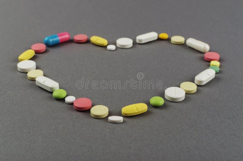 Coração criado dos comprimidos coloridos Conceito MÉDICO foto de stock