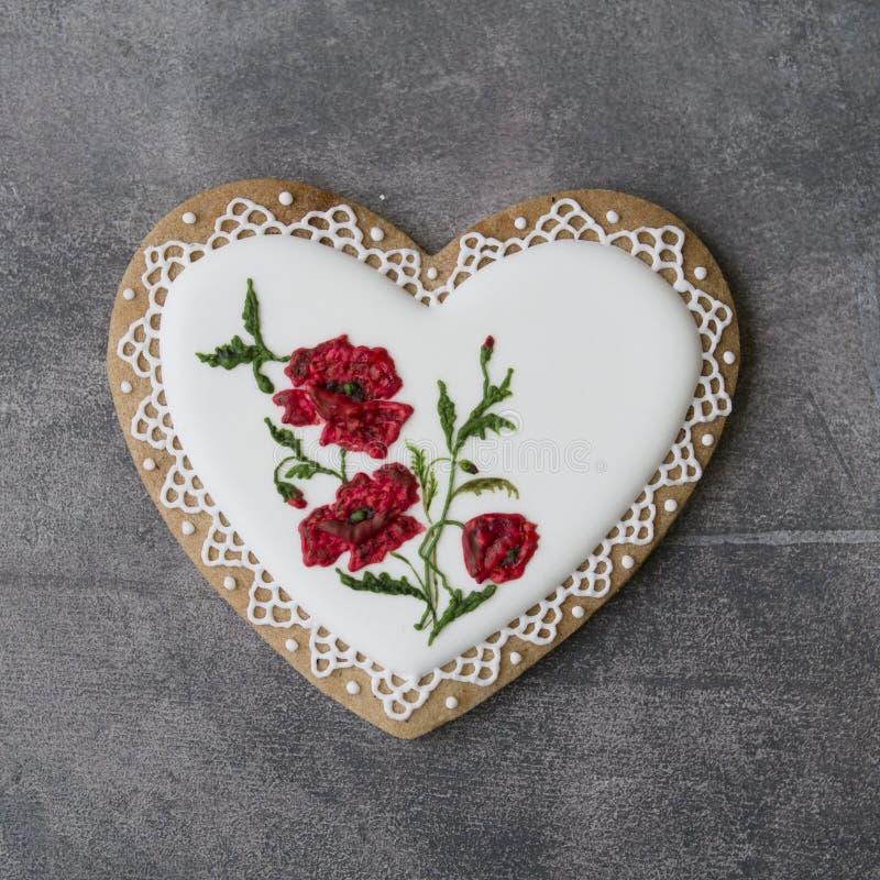 Coração da cookie do Valentim decorado com as papoilas vermelhas no estilo do vintage no fundo cinzento para o dia de Valentim, o fotos de stock