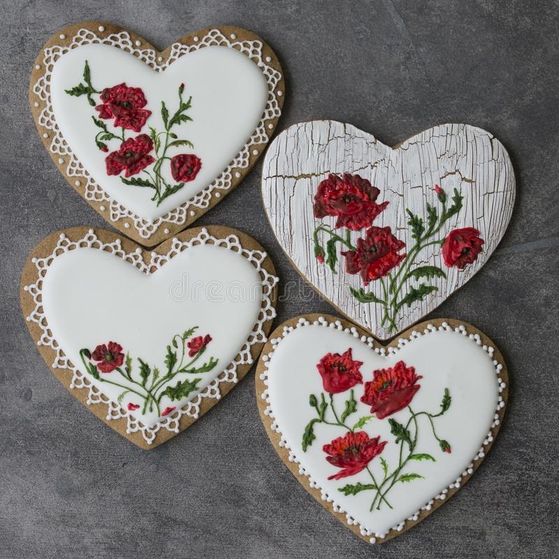 Coração da cookie do Valentim decorado com as papoilas vermelhas no estilo do vintage no fundo cinzento para o dia de Valentim, o imagem de stock