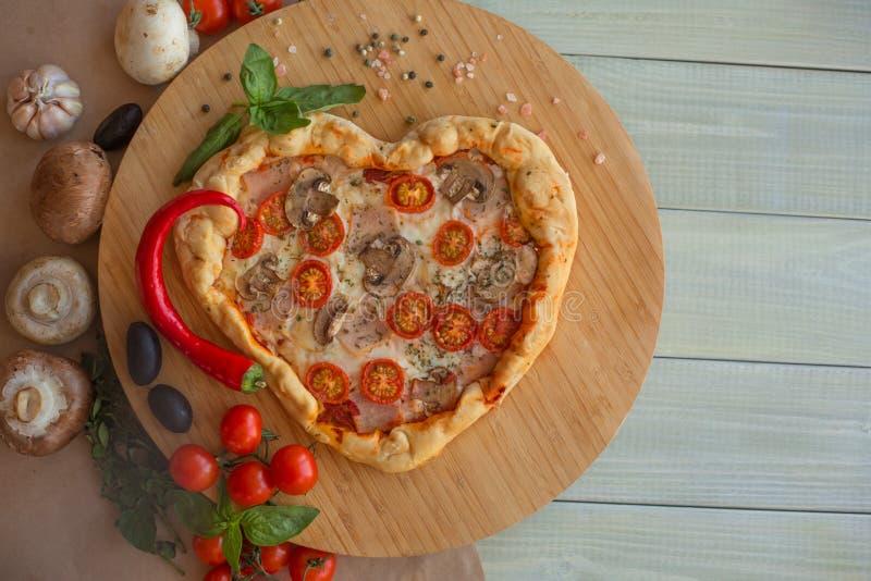 Coração da pizza dado forma na madeira fotografia de stock royalty free