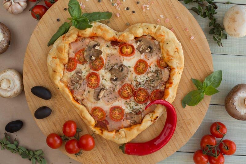 Coração da pizza dado forma na madeira imagem de stock royalty free