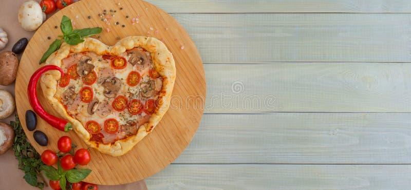 Coração da pizza dado forma na madeira imagens de stock