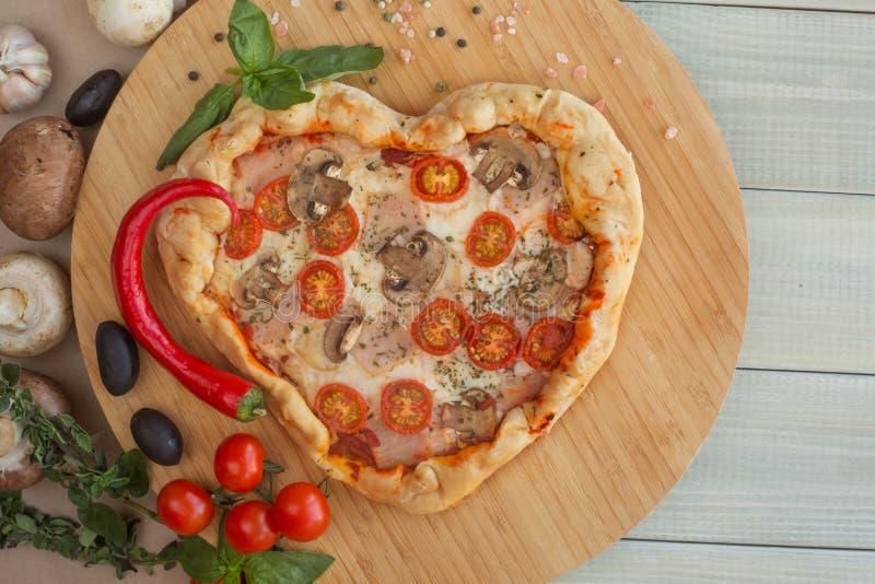 Coração da pizza dado forma na madeira fotos de stock royalty free
