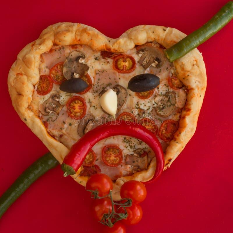 Coração da pizza dado forma no vermelho fotografia de stock