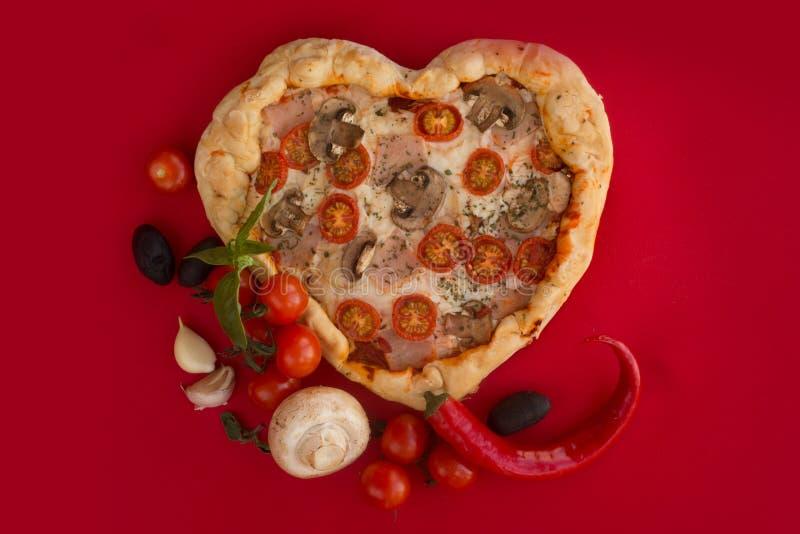 Coração da pizza dado forma no vermelho foto de stock