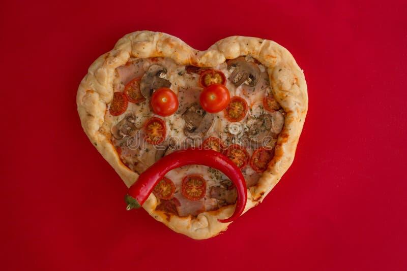 Coração da pizza dado forma no vermelho imagem de stock royalty free