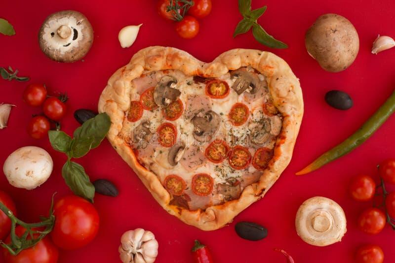 Coração da pizza dado forma no vermelho fotografia de stock royalty free