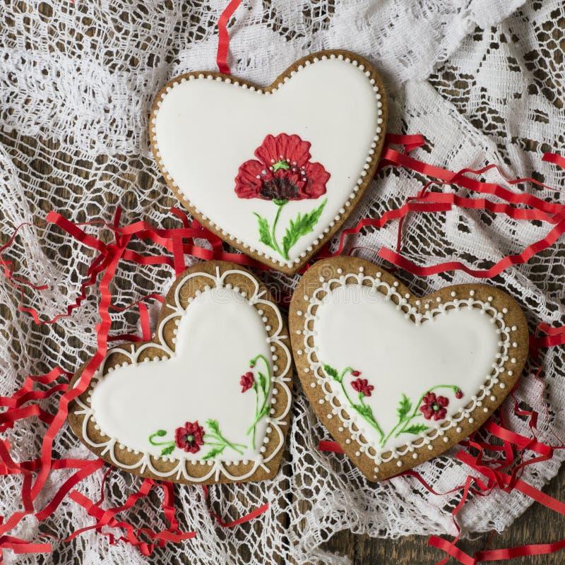 Coração das cookies decorado com as papoilas vermelhas no estilo do vintage no fundo de madeira para o dia de Valentim Presente p imagens de stock