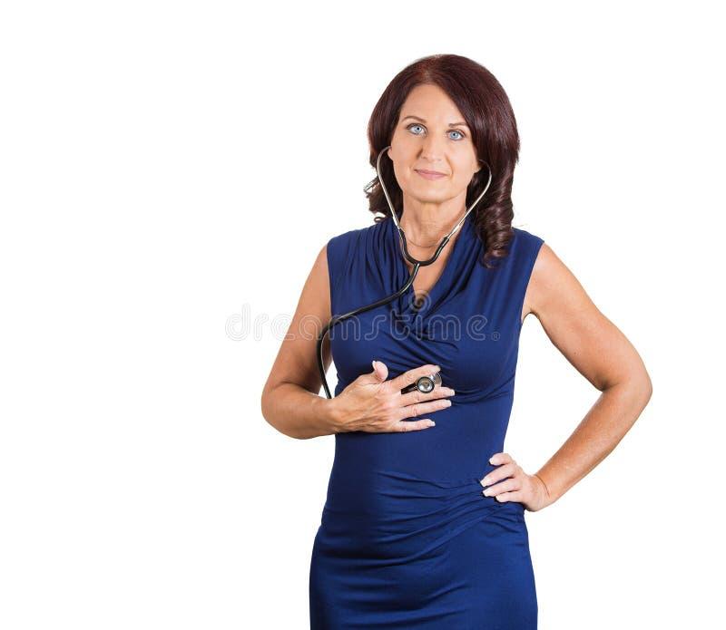Coração de escuta da mulher com estetoscópio foto de stock royalty free