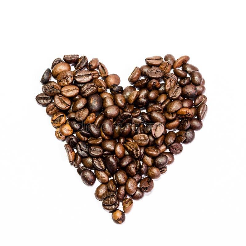 Coração de feijões pretos do café em um fundo branco fotografia de stock royalty free