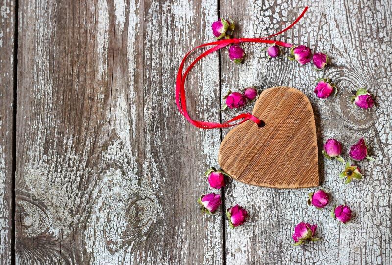 Coração de madeira com fita vermelha e rosebuds secados pequenos em um woode foto de stock
