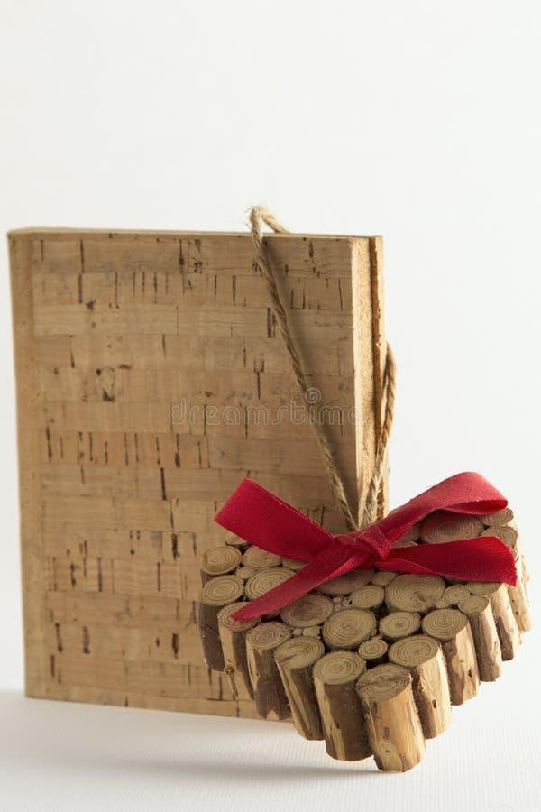 Coração de madeira dos nós do Natal em livros da cortiça imagem de stock