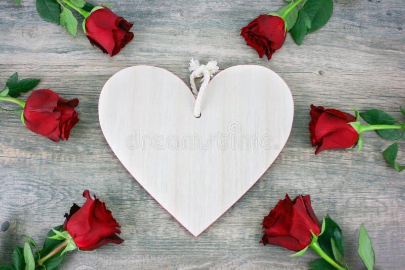 Coração de madeira rústico e rosas vermelhas sobre o fundo de madeira para o feriado do dia de Valentim imagem de stock