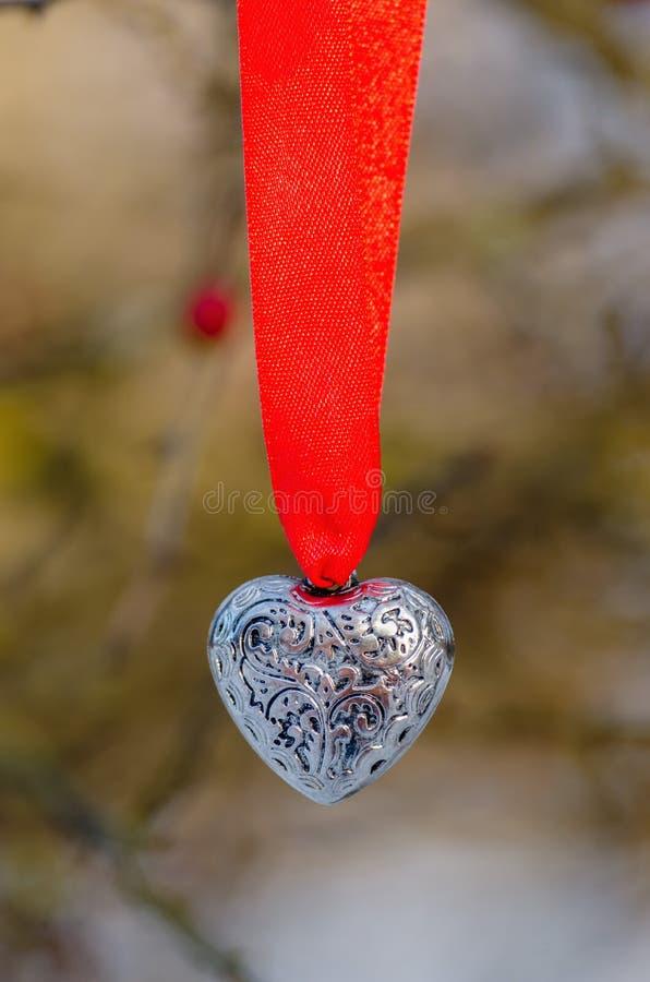 Coração de prata em uma fita vermelha foto de stock