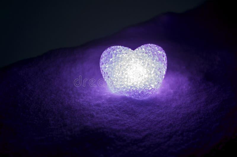 coração de vidro abstrato na neve na noite Cartão para o dia de um Valentim llight violeta do coração no fundo preto foto de stock