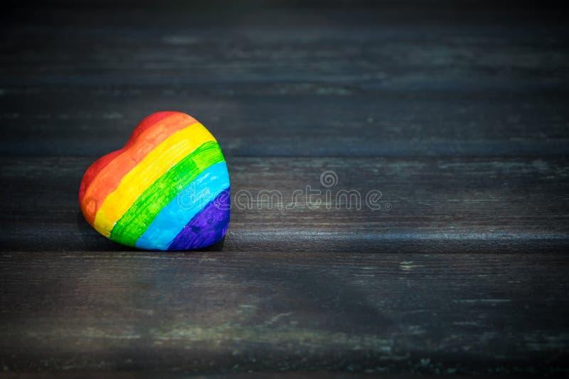 Coração decorativo com as listras do arco-íris no fundo de madeira escuro Bandeira do orgulho de LGBT, símbolo de lésbica, alegre foto de stock royalty free