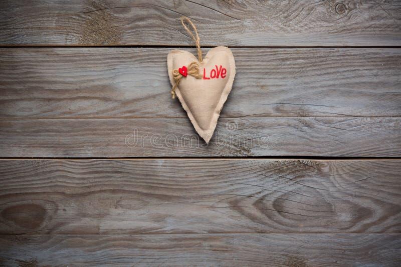 Coração decorativo de matéria têxtil com amor da inscrição no fundo de madeira rústico das pranchas O dia de Valentim, comemorand imagem de stock
