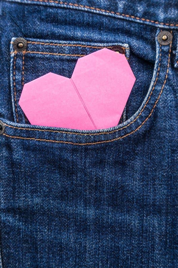 Coração do origâmi no bolso azul de brim fotos de stock