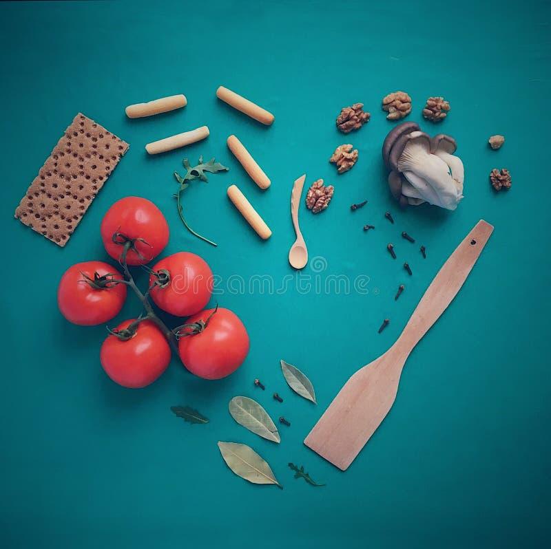 Coração do pão e dos tomates com porcas e folhas foto de stock
