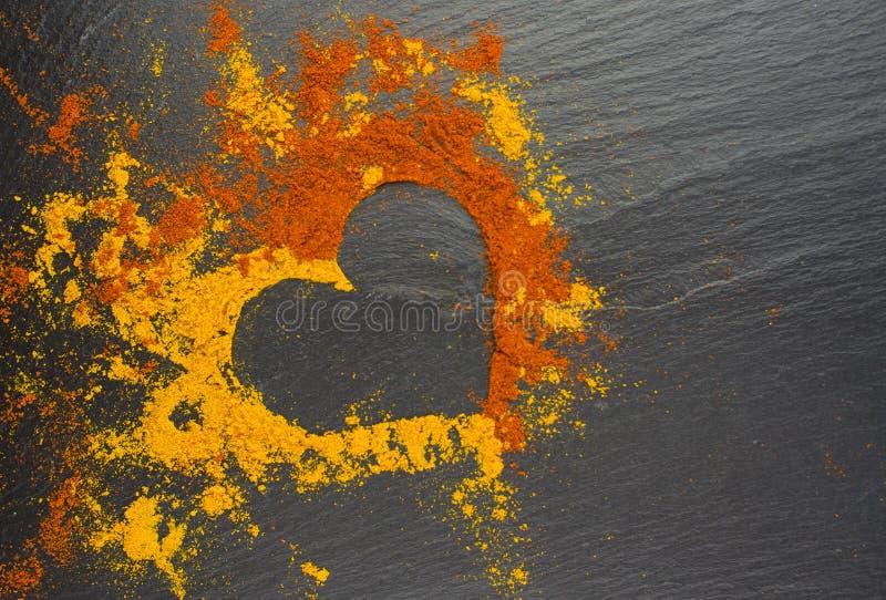Coração do Valentim das especiarias caril e paprika no fundo preto 14 de fevereiro foto de stock