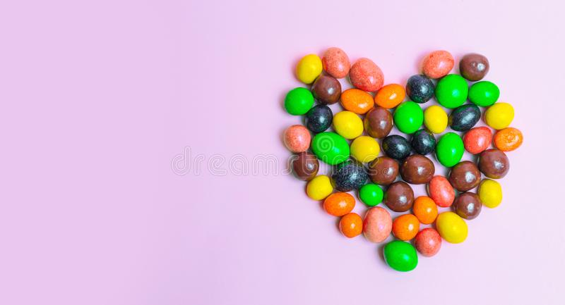 Coração dos doces, doces coloridos em um fundo cor-de-rosa, alimento doce O conceito do amor bandeira Copie o espaço fotos de stock