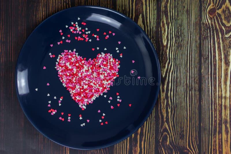 Coração dos doces multi-coloridos pequenos Em uma placa azul Dia do `s do Valentim Cartão do Valentim imagem de stock royalty free