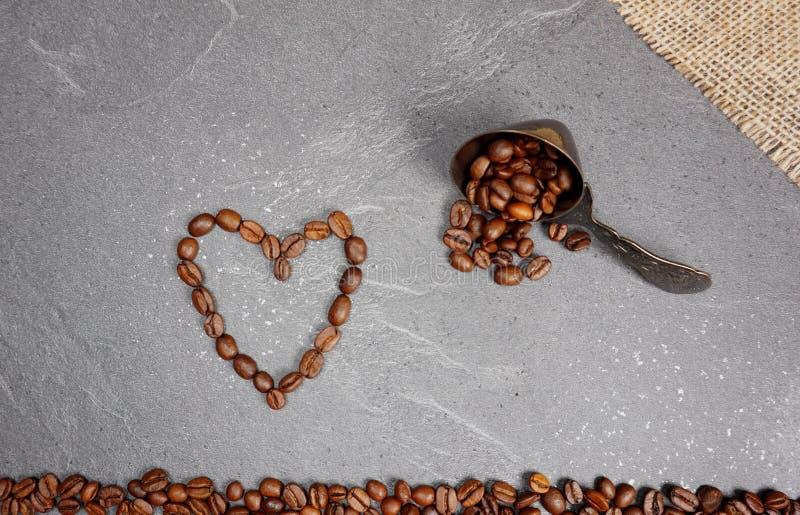 Coração dos feijões de café com serapilheira e colher no fundo cinzento do worktop da cozinha foto de stock