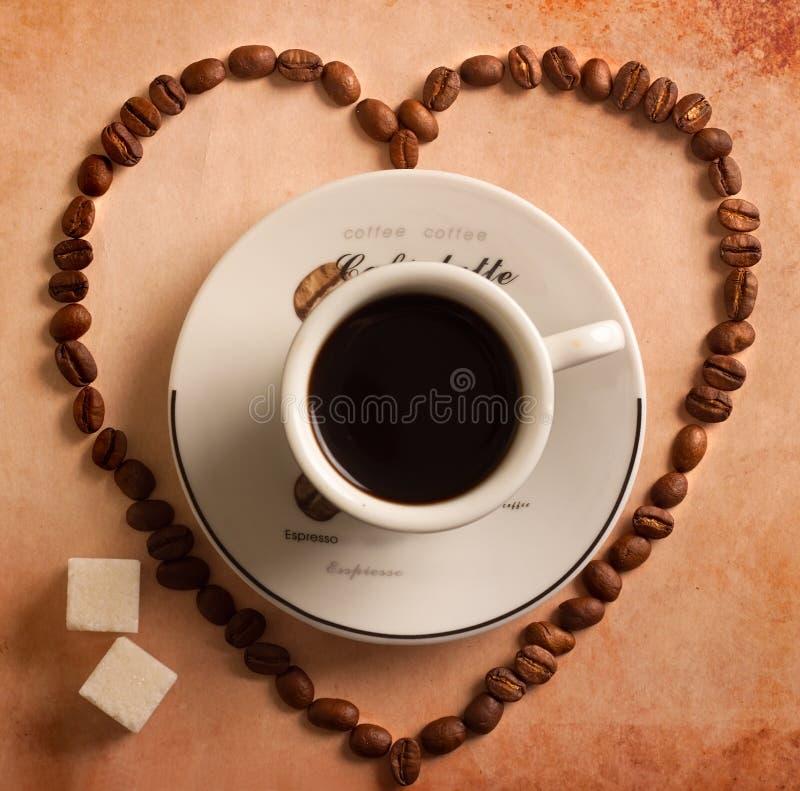 Coração dos feijões de café em torno do copo fotografia de stock