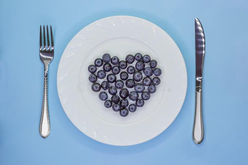 Coração dos mirtilos na placa branca com cutelaria Conceito da dieta do vegetariano do amor Dia do `s do Valentim foto de stock royalty free