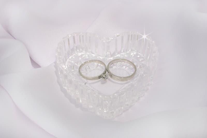Coração e anéis de casamento de cristal imagens de stock royalty free