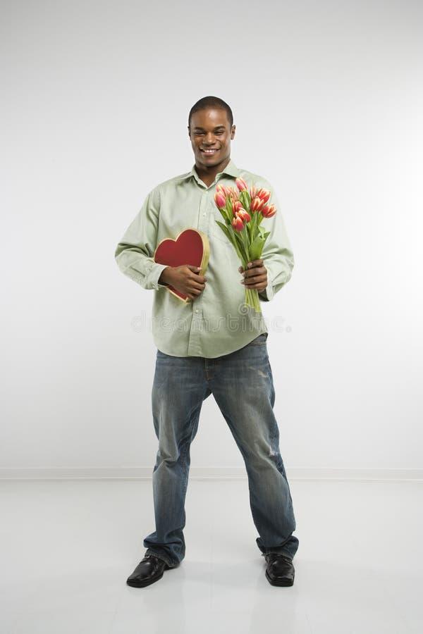 Coração e flores da terra arrendada do homem. fotografia de stock royalty free