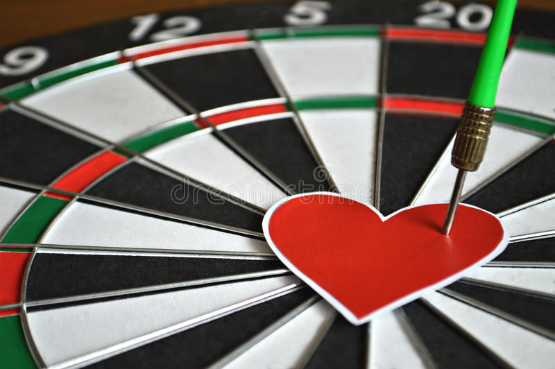 Coração e seta na placa de dardo imagem de stock