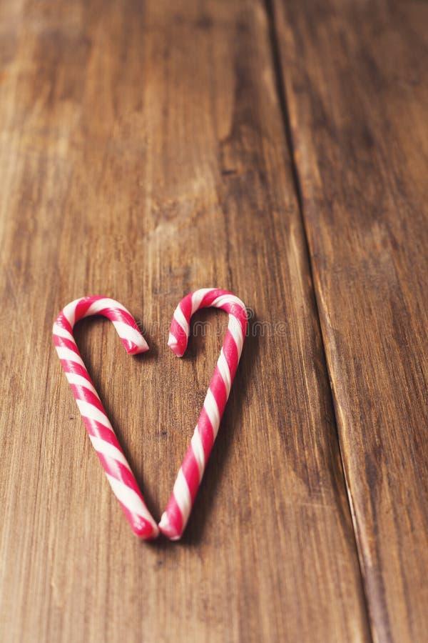 Coração em honra do dia do ` s do Valentim feito do bastão de doces em um fundo de pranchas de madeira velhas fotografia de stock
