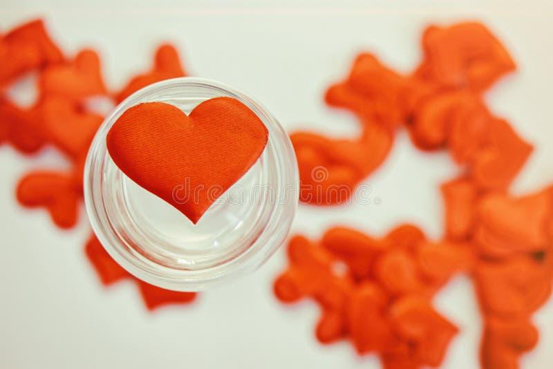 Coração em um vidro transparente enchido com água St Dia do ` s do Valentim Felicitações no dia do ` s do Valentim imagem de stock