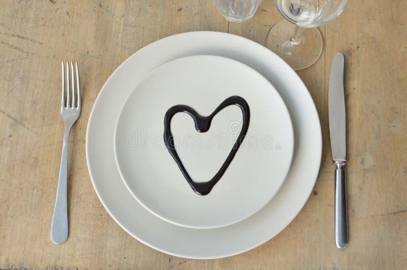 Coração em uma placa Tabela de madeira cutlery Faca, forquilha Vidros Apropriado como um fundo Para o menu Nós amamos com amor imagem de stock royalty free