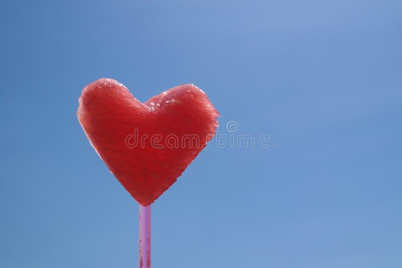 Coração encantador bonito suculento vermelho da melancia no fundo do céu azul fotos de stock