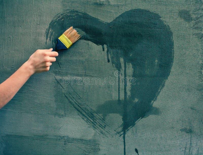 Coração fêmea da pintura da mão na parede imagem de stock royalty free