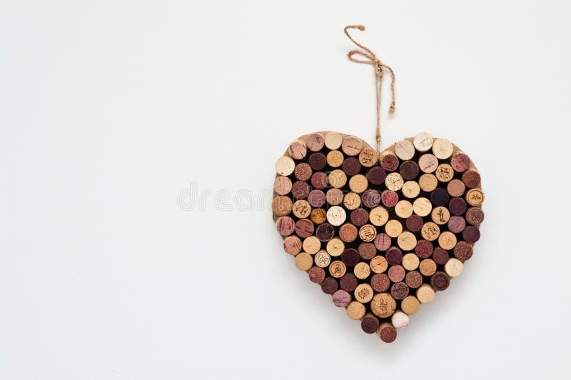 Coração feito das cortiça do vinho isoladas na parede branca foto de stock royalty free