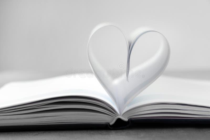 Coração feito das folhas de papel no livro foto de stock