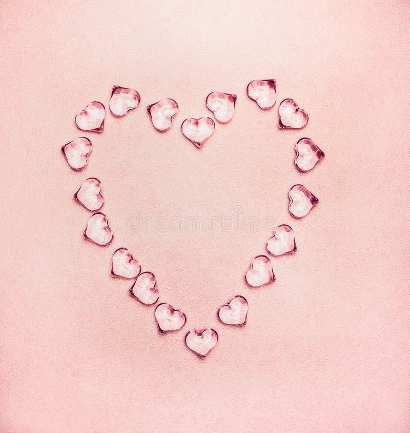 Coração feito dos corações de vidro em pálido - fundo cor-de-rosa imagens de stock royalty free