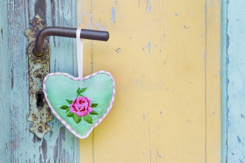 Coração feito a mão da tela que pendura em um puxador da porta velho por um verão imagens de stock royalty free