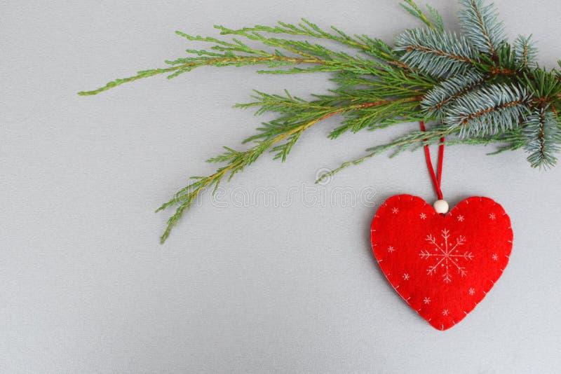 Coração feito a mão vermelho no ramo de árvore do xmas foto de stock