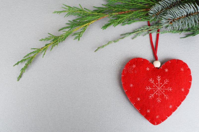 Coração feito a mão vermelho no ramo de árvore do xmas fotos de stock