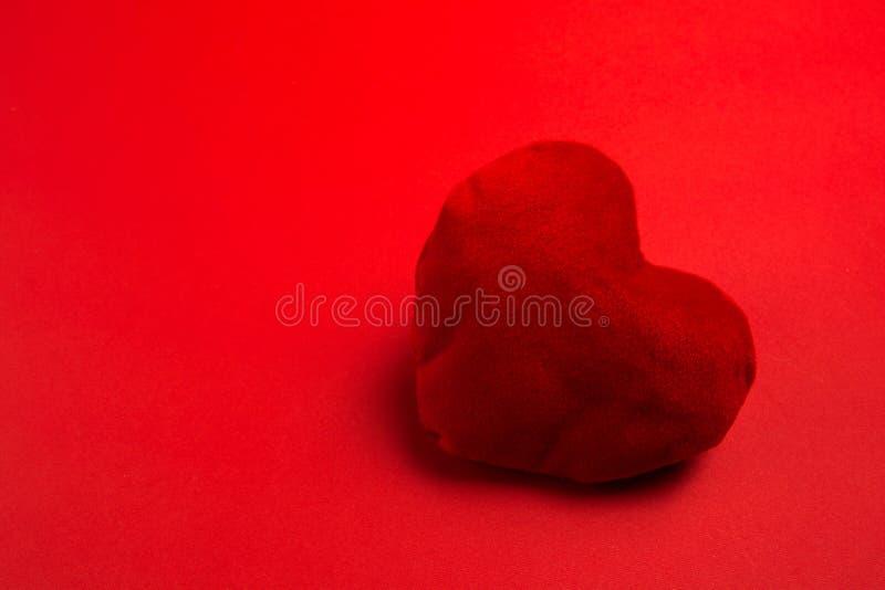 Coração macio vermelho no fundo vermelho fotos de stock