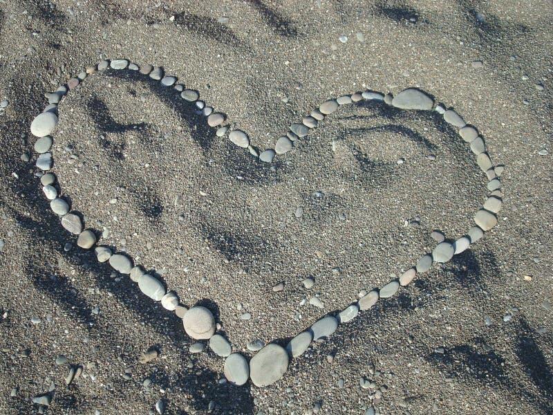 Coração na areia das pedras imagens de stock royalty free