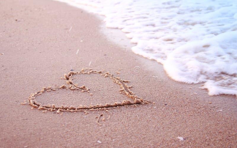 Coração na areia no litoral fotografia de stock
