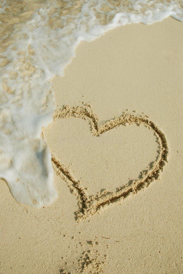 Coração na praia arenosa fotografia de stock royalty free