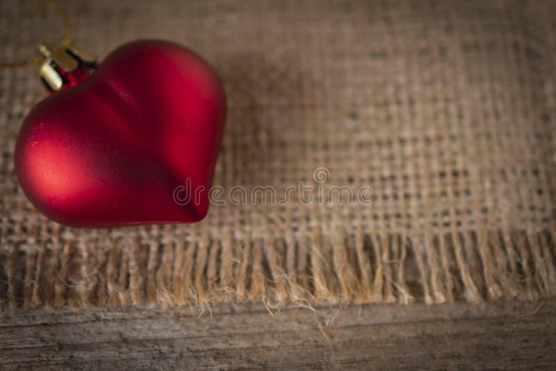 Coração plástico vermelho colocado no saco e na tabela de madeira imagem de stock