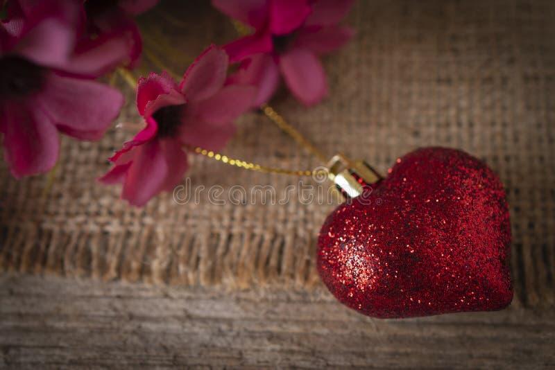 Coração plástico vermelho colocado no saco Há uma flor colocada na parte traseira esquerda imagens de stock